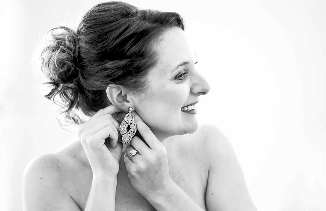 Black and white wedding photography of a bride putting on her jewelery.