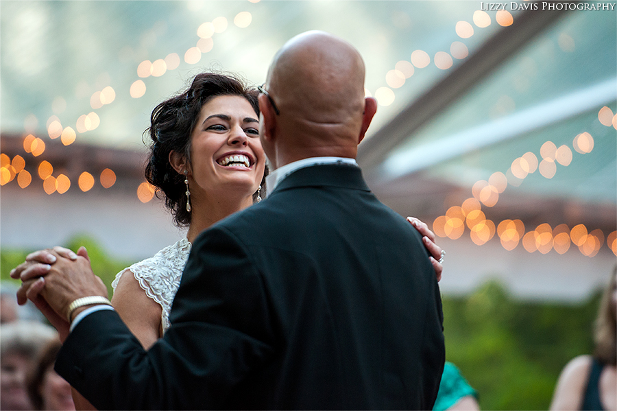 Photo of a smiling bride dancing with her father.